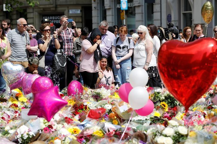 People react as they look at floral tributes for the victims of the Manchester Arena attack,in St Ann's Square, in central Manchester, Britain May 25, 2017. REUTERS/Darren Staples