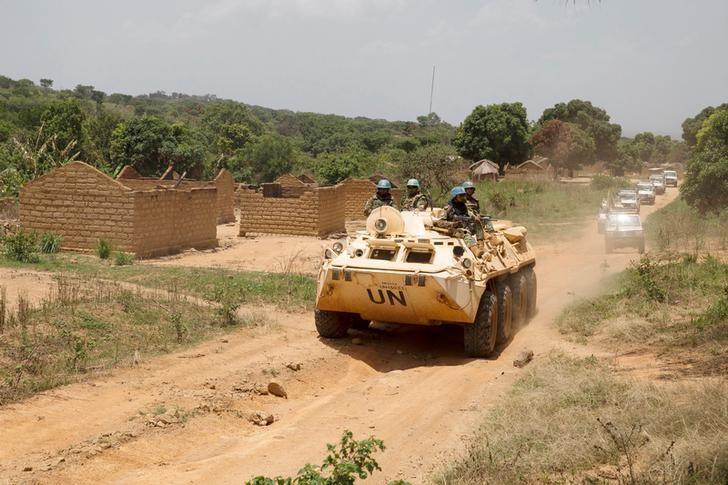 United Nations peacekeeping force vehicles drive by houses destroyed by violence in September, in the abandoned village of Yade, Central African Republic April 27, 2017. Picture taken April 27, 2017 REUTERS/Baz Ratner