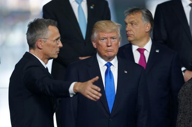 NATO Secretary General Jens Stoltenberg (L) directs U.S President Donald Trump who takes his place as NATO member leaders gather before the start of their summit in Brussels, Belgium, May 25, 2017.    REUTERS/Hannibal Hanschke