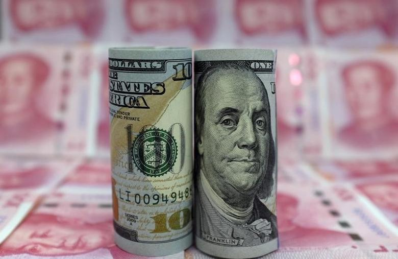 资料图片:2016年1月,以人民币纸币为背景拍摄的美元纸币。REUTERS/Jason Lee
