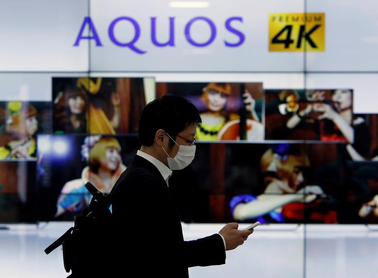 FILE PHOTO: A man using his mobile phone walks past Sharp Corp's liquid crystal display monitors showing the company's Aquos television in Tokyo, Japan, March 30, 2016. REUTERS/Yuya Shino/File Photo