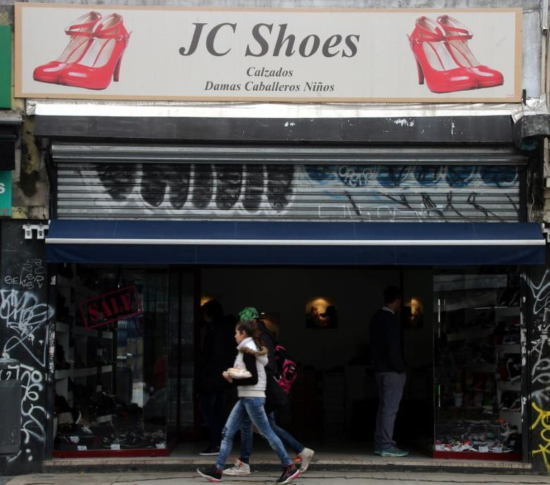 People walk past a shoe store in Buenos Aires, Argentina, May 19, 2017. REUTERS/Marcos Brindicci - RTX36NMZ