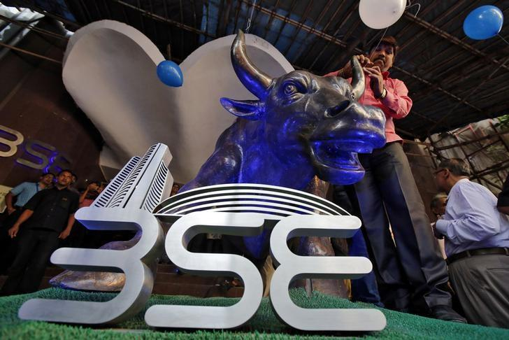 FILE PHOTO: A man ties a balloon to the horns of a bull statue at the entrance of the Bombay Stock Exchange (BSE) while celebrating the Sensex index rising to over 30,000, in Mumbai, India April 26, 2017. REUTERS/Shailesh Andrade/File Photo