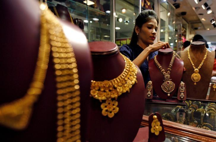A salesperson attends to a customer (not pictured) inside a jewellery showroom, during Akshaya Tritiya, a major gold-buying festival, in Mumbai, India April 28, 2017. REUTERS/Shailesh Andrade/File Photo