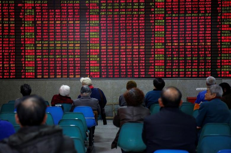 Investors look at an electronic board showing stock information on the first trading day after the New Year holiday at a brokerage house in Shanghai, China, January 3, 2017.  REUTERS/Aly Song