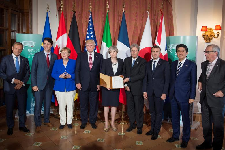 European Council President Donald Tusk, Canadian Prime Minister Justin Trudeau, German Chancellor Angela Merkel, U.S. President Donald Trump, Britain's Prime Minister Theresa May, Italian Prime Minister Paolo Gentiloni, French President Emmanuel Macron, Japanese Prime Minister Shinzo Abe,  and European Commission President Jean-Claude Juncker pose after signing the 'G7 Taormina Statement on the Fight Against Terrorism and Violent Extremism' at the G7 summit in Taormina, Sicily, Italy, May 26, 2017. Guido Bergmann/Courtesy of Bundesregierung/Handout via REUTERS
