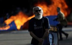 """A demonstrator shows a picture of President Michel Temer near a burning barricade during a protest against Temer and the latest corruption scandal to hit the country, in Brasilia, Brazil, May 24, 2017. Picture taken May 24, 2017. The sign reads: """"Out Temer!."""" REUTERS/Ueslei Marcelino"""