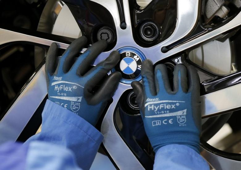 FILE PHOTO - A worker mounts the logo on a rim at the serial production BMW i3 electric car in the BMW factory in Leipzig September 18, 2013.  REUTERS/Fabrizio Bensch