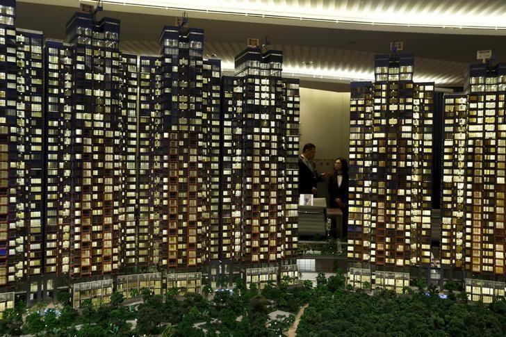 资料图片:2015年3月,香港一处售楼中心的售楼人员在住宅楼模型后交谈。REUTERS/Bobby Yip