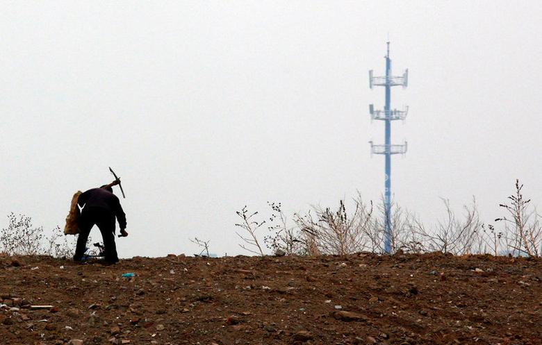 FILE PHOTO: A mobile phone tower is seen behind a man carrying a pick over his shoulder as he walks past an area that will soon be a construction site on the outskirts of Beijing April 25, 2011.    REUTERS/David Gray/File Photo