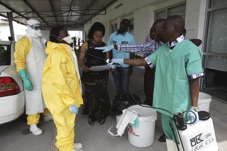 FILE PHOTO: A health worker sprays a colleague with disinfectant during a training session for Congolese health workers to deal with Ebola virus in Kinshasa October 21, 2014. REUTERS/Media Coulibaly