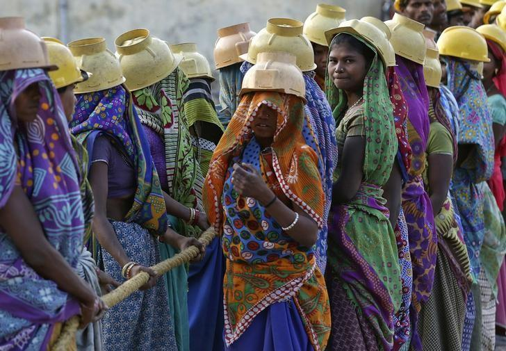 Female labourers wearing helmets take a break from laying underground electricity cables in Ahmedabad, March 7, 2016. REUTERS/Amit Dave/Files