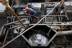 The flow of crude oil is seen in a container while an oilfield worker works on a drilling rig at an oil well operated by Venezuela's state oil company PDVSA, in the oil rich Orinoco belt, near Cabrutica at the state of Anzoategui April 16, 2015. Venezuela has launched talks this month on a novel plan to blend the country's heavy crude with light oil from other OPEC allies, seeking to create a new variety that can compete against swelling U.S. and Canadian supplies. The proposal, which would expand on a pilot scheme involving Algerian oil last year, envisions supplying refineries built for medium-grade crudes rather than the light oil that has become plentiful as a result of the North American shale boom, said the head of state oil company PDVSA, Eulogio del Pino. Picture taken on April 16, 2015. REUTERS/Carlos Garcia Rawlins