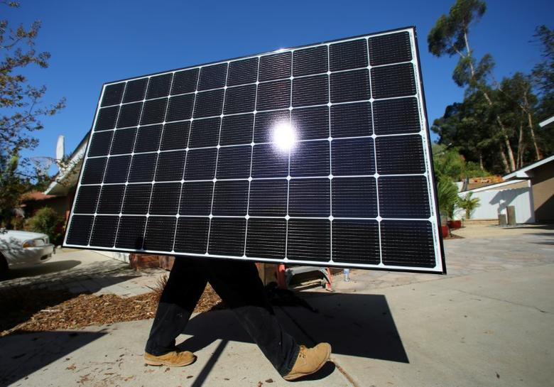 A solar installer carries a solar panel during an installation  at a residential home in Scripps Ranch, San Diego, California, U.S. October 14, 2016. Picture taken October 14, 2016.       REUTERS/Mike Blake