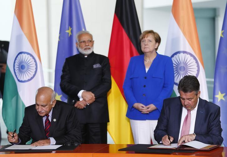 German Foreign Minister Sigmar Gabriel and India's Minister of State for External Affairs Mobashar Jawad Akbar sign documents next to Indian Prime Minister Narendra Modi and German Chancellor Angela Merkel at a ceremony during the 4th round of German-Indian government consultation at the Chancellery in Berlin, Germany, May 30, 2017. REUTERS/Hannibal Hanschke