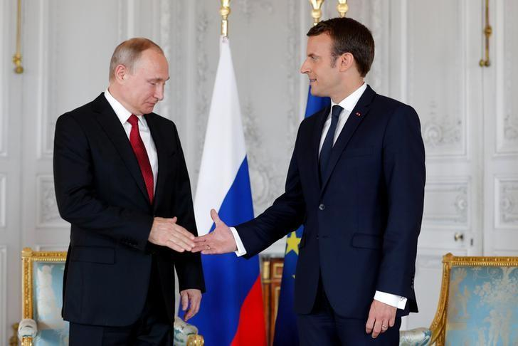 French President Emmanuel Macron shakes hands Russian President Vladimir Putin (L) at the Chateau de Versailles as they meet for talks before the opening of an exhibition marking 300 years of diplomatic ties between the two countyies in Versailles, France, May 29, 2017.   REUTERS/Philippe Wojazer