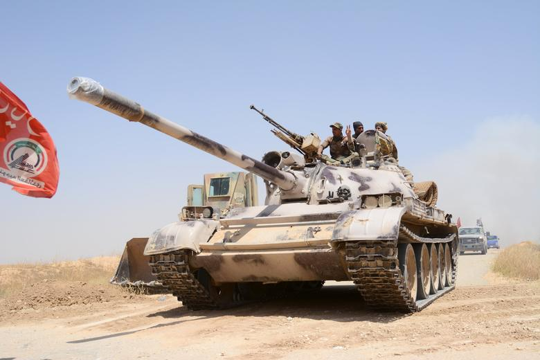 FILE PHOTO: Popular Mobilization Forces (PMF) ride on a tank during a battle with Islamic State militants, at Um Jaris village on the Iraqi border with Syria, Iraq May 29, 2017.  REUTERS/Stringer/File Photo