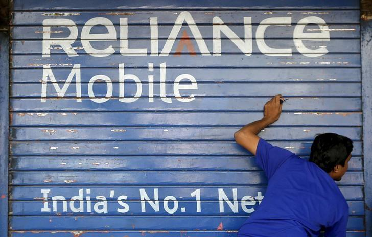 A man opens the shutter of a shop painted with an advertisement of Reliance Communications in Mumbai, November 3, 2015. REUTERS/Shailesh Andrade/Files