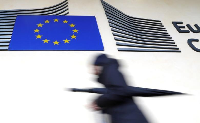 A woman walks past the European flag outside the EU Commission headquarters in Brussels, Belgium March 1, 2017. REUTERS/Yves Herman