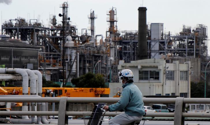 FILE PHOTO: A worker cycles near a factory at the Keihin industrial zone in Kawasaki, Japan, March 8, 2017.      REUTERS/Toru Hanai/File Photo
