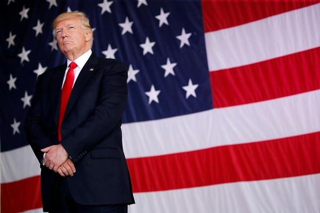 U.S. President Donald Trump stands in front of a U.S. flag while listening to U.S. first lady Melania Trump give a speech to U.S. troops at the Naval Air Station Sigonella before returning to Washington D.C. at Sigonella Air Force Base in Sigonella, Sicily, Italy, May 27, 2017. REUTERS/Jonathan Ernst/Files