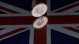 """Монета в 1 фунт на фоне британского флага. Британский фунт развернулся в сторону роста после снижения на 0,5 процента в среду благодаря результатам предвыборного опроса, показавшего, что правящая Консервативная партия страны по-прежнему занимает ведущие позиции, перечёркивая предыдущие ожидания """"подвешенного"""" парламента. REUTERS/Darren Staples"""