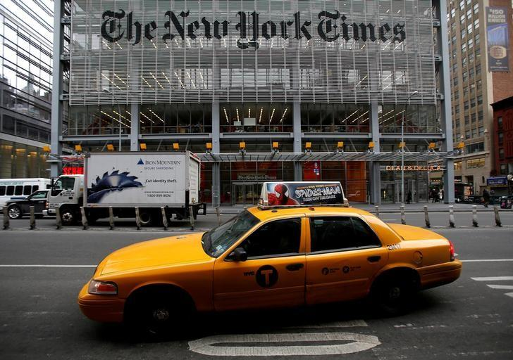 A taxi passes by in front of The New York Times head office in New York, February 7, 2013. REUTERS/Carlo Allegri/Files