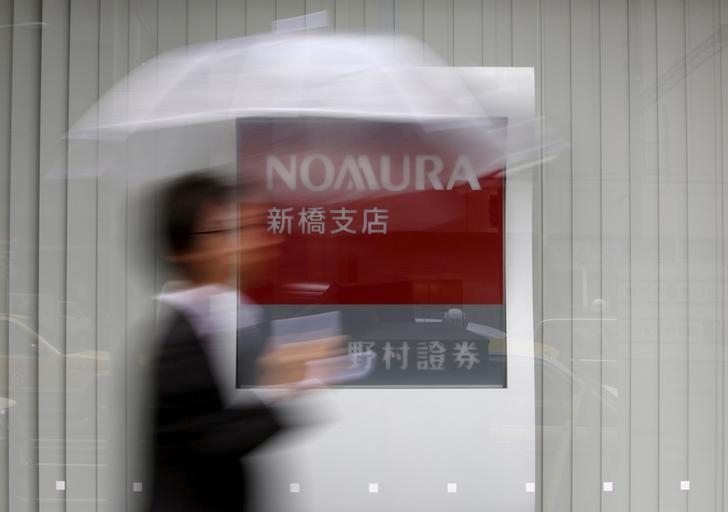 FILE PHOTO: A man holding an umbrella walks in front of a signboard of Nomura Securities outside its branch in Tokyo October 29, 2013.   REUTERS/Issei Kato/File Photo