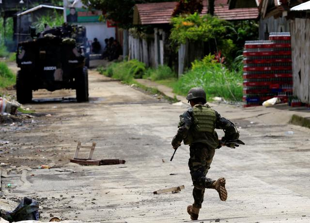 A government soldier runs towards his colleague. REUTERS/Romeo Ranoco
