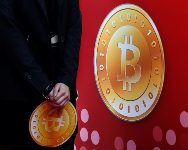 6月1日、ビットコインの乱高下が続く中、ドルや円などの通貨に影響が及ぶのかという点にも、関心が集まり出している。写真は香港の店舗で2014年2月撮影(2017年 ロイター/Bobby Yip)
