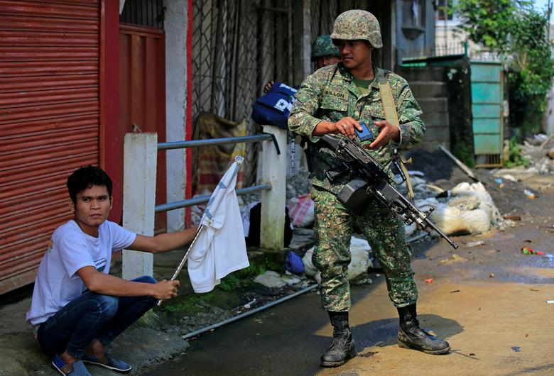 A government soldier looks at a man holding a white flag who fled his home as government troops continue their assault on insurgents from the Maute group, who have taken over large parts of the Marawi City, Philippines June 1, 2017. REUTERS/Romeo Ranoco