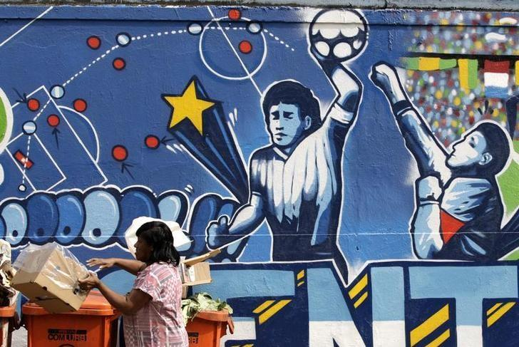 A resident stands near a mural depicting the famous ''Hand of God'' goal by former Argentine soccer star Diego Maradona, in light of the upcoming 2010 FIFA World Cup at the Agua Santa neighborhood in Rio de Janeiro May 21, 2010.  REUTERS/Sergio Moraes/Files