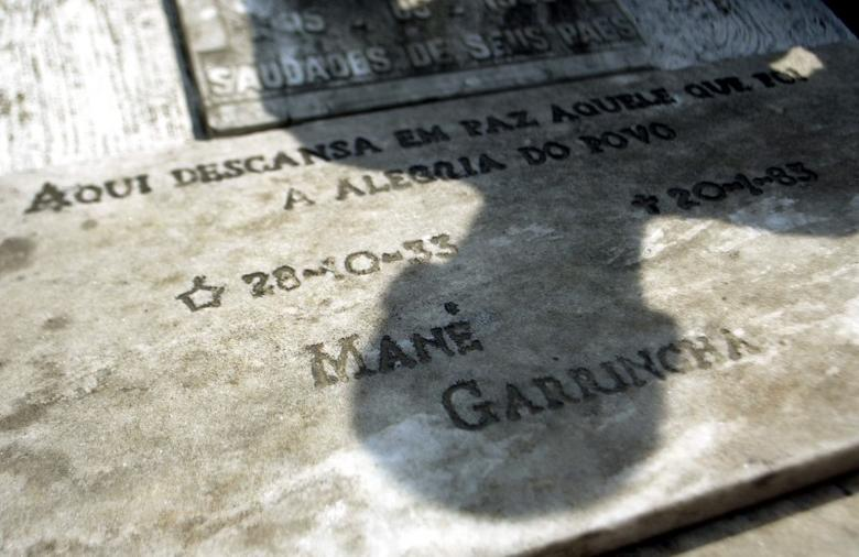 A man casts his shadow over the grave of former Brazilian soccer player Mane Garrincha, with an inscription that's read: ''Here rests in peace the one who was the Joy of the People - Mane Garrincha,'' at cemetery in Pau Grande city near Rio de Janeiro, this pictures taken on September 23, 2004. REUTERS/Bruno Domingos  BD