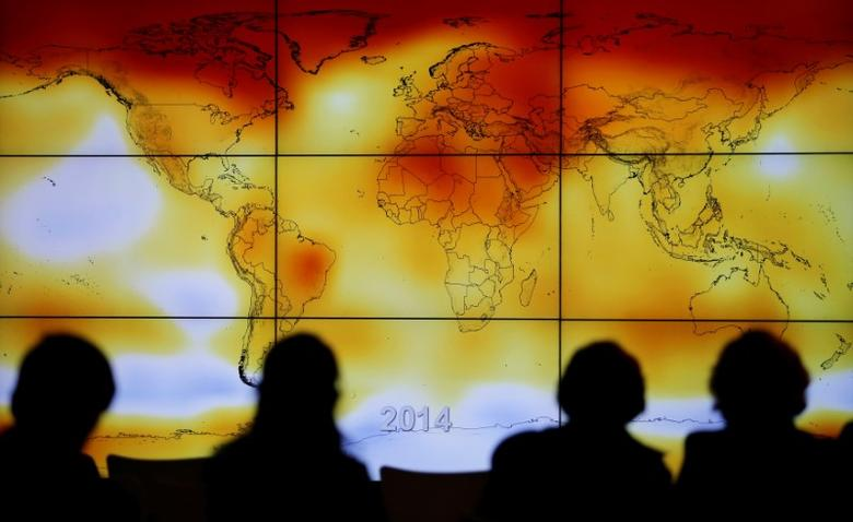 FILE PHOTO: Participants are seen in silhouette as they look at a screen showing a world map with climate anomalies during the World Climate Change Conference 2015 (COP21) at Le Bourget, near Paris, France, December 8, 2015.  REUTERS/Stephane Mahe