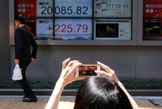 Una donna fa un selfie davanti a un tabellone elettronico che mostra l'andamento dell'azionario a Tokyo.  REUTERS/Toru Hanai