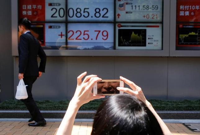 6月2日、日経平均がようやく2万円の大台を突破した。良好な景気や堅調な企業業績見通しが、米株最高値更新という追い風を受けて再評価された形だが、約4週間、大台手前で「じらされた」エネルギーが噴き出した面もある。都内の証券会社で撮影(2017年 ロイター/Toru Hanai)