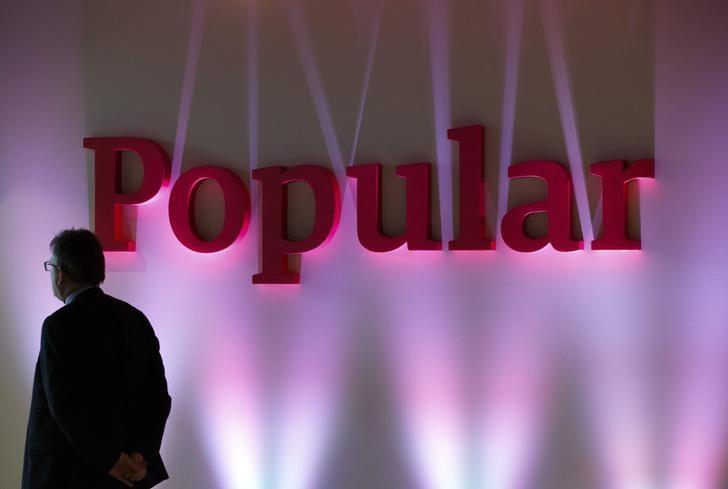 A man stands next to the logo of Spain's Banco Popular during the bank's results presentation in Madrid January 30, 2015. Banco Popular said on Friday that net profit rose 31 percent in 2014 from a year earlier, even as earnings from its lending business shrank. REUTERS/Sergio Perez/Files