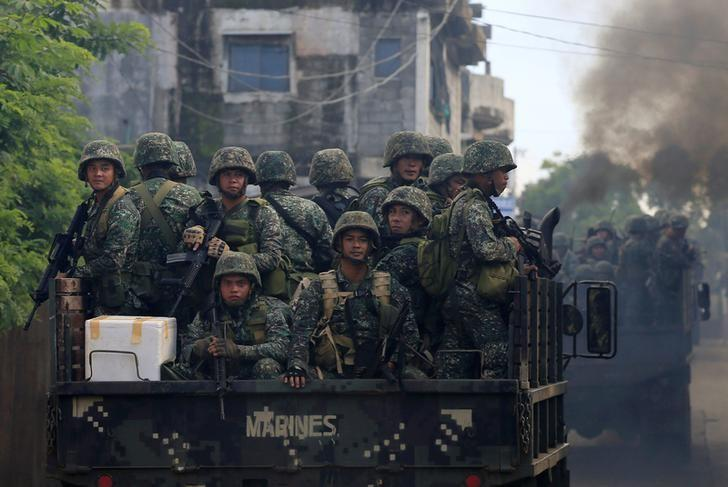 Soldiers onboard military trucks ride along the main street as government troops continue their assault on insurgents from the Maute group, who have taken over large parts of Marawi City, Philippines June 2, 2017. REUTERS/Romeo Ranoco