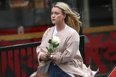 A woman cries as she carries a tribute to leave on London Bridge, after an attack left 7 people dead and dozens injured, in London, Britain June 4, 2017. REUTERS/Neil Hall