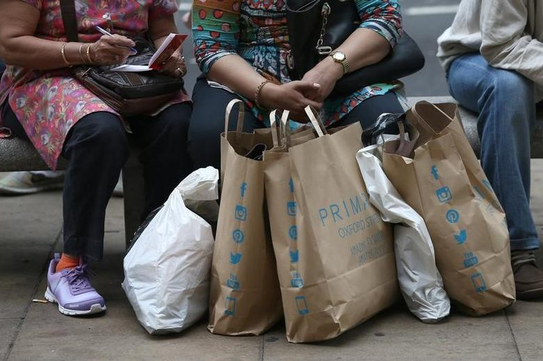 FILE PHOTO: Shoppers sit with bags in London, Britain August 25, 2016. REUTERS/Neil Hall