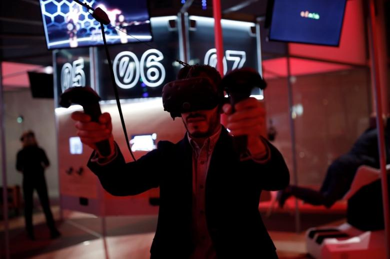 A man uses HTC Vive Virtual Reality (VR) headset at the mk2 VR, a place dedicated to virtual reality in Paris, France, December 5, 2016. REUTERS/Benoit Tessier