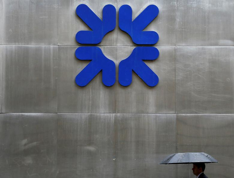 FILE PHOTO: A man shelters under an umbrella as he walks past a branch of the Royal Bank of Scotland in London, Britain, September 17, 2013. REUTERS/Stefan Wermuth/File Photo