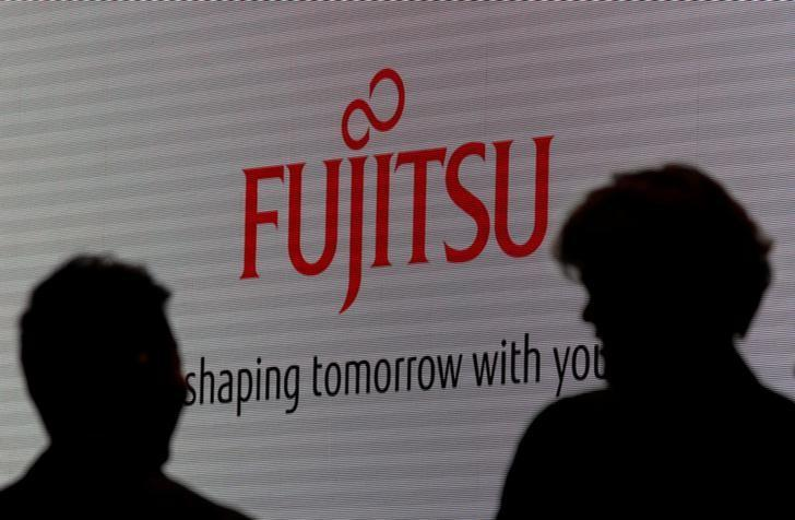 FILE PHOTO: People are silhouetted against a screen displaying a logo of Fujitsu at CEATEC JAPAN 2012 electronics show in Chiba, east of Tokyo, October 2, 2012.   REUTERS/Yuriko Nakao/File Photo