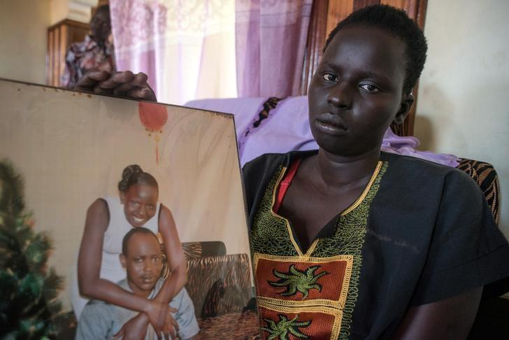 South Sudanese Rebecca Chuol Ungdeng, poses for a photograph during a Reuters interview in Uganda's capital Kampala in this picture taken May 4, 2017, with a portrait of her and her late husband John Gatluak, a South Sudanese aid worker who was killed by government soldiers during the attack on the Terrain hotel compound in Juba, South Sudan on July 11, 2016. REUTERS/Stringer