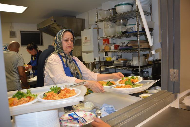 A volunteer serves up plates of food made from food waste during a Ramadan meal in London, 3 June 2017. Thomson Reuters Foundation/Adela Suliman
