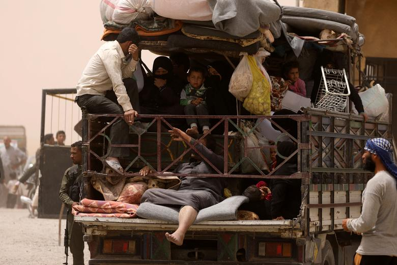 FILE PHOTO: Internally displaced people who fled Raqqa city ride a vehicle with their belongings in a camp near Ain Issa, Raqqa Governorate, Syria May 19, 2017. Picture taken May 19, 2017. REUTERS/Rodi Said/File Photo