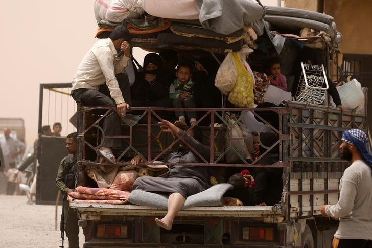 Internally displaced people who fled Raqqa city ride a vehicle with their belongings in a camp near Ain Issa, Raqqa Governorate, Syria May 19, 2017. REUTERS/Rodi Said/Files