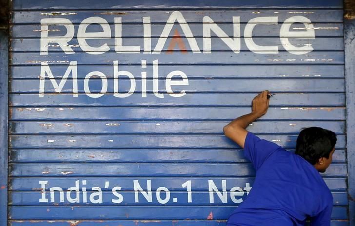 A man opens the shutter of a shop painted with an advertisement of Reliance Communications in Mumbai, India, November 3, 2015.   REUTERS/Shailesh Andrade/File Photo