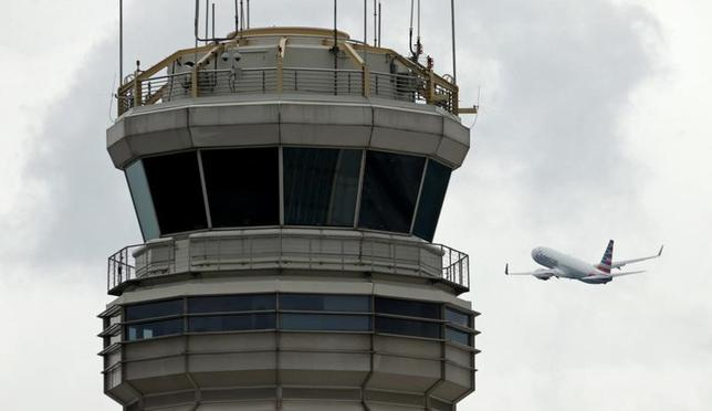 A plane passes the air traffic control tower at Ronald Reagan Washington National Airport in Arlington, Virginia, U.S., June 5, 2017.  REUTERS/Kevin Lamarque