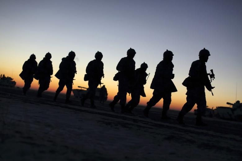 Soldiers of the People's Liberation Army (PLA) Marine Corps march during a military drill as the sun rises at a military base in Taonan, Jilin province January 28, 2015. REUTERS/China Daily